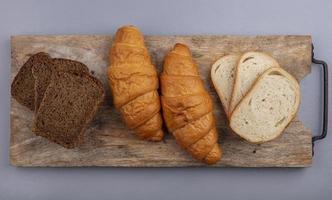 skivat bröd på skärbräda på grå bakgrund