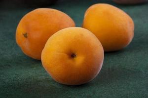 närbild av persikor på en grön bakgrund foto