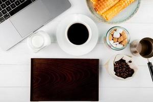 ovanifrån av en kopp kaffe med rån rullar nära bärbar dator foto