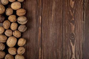 ovanifrån av hela valnötter utspridda på träbakgrund med kopieringsutrymme