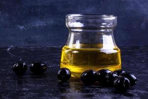 framifrån av svarta oliver med olivolja i en glasburk på en svart bakgrund foto