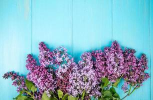 ovanifrån av lila blommor isolerad på blå trä bakgrund med kopia utrymme foto