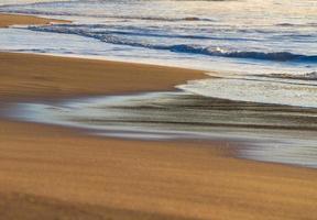 tidsfördröjning av vågor på stranden foto