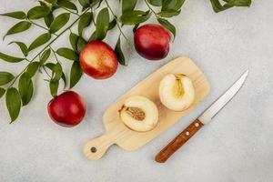 ovanifrån av en halvskuren persika på skärbräda