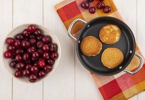 ovanifrån av pannkakor på rutigt tyg och i skål på träbakgrund