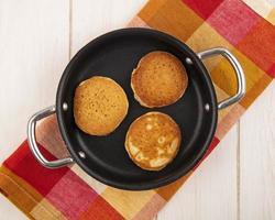 ovanifrån av pannkakor i panna på rutigt tyg och träbakgrund