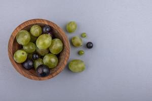 ovanifrån av druvbär i skål på grå bakgrund med kopieringsutrymme foto