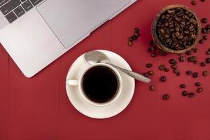ovanifrån av färskt rostat kaffe bredvid bönor och en bärbar dator foto