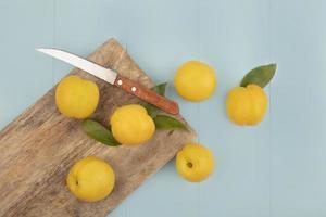 ovanifrån av färska gula persikor isolerad på en trä köksplatta med kniv på en blå bakgrund