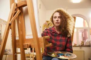 ganska rödhårig lockig konstnär fokuserad ritar en målning
