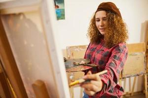 lockig konstnär ler och ritar en bild