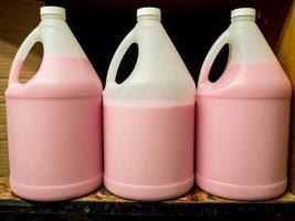 flytande handtvål rosa plastflaskor vaktmästare sanitizer hylla handtag foto
