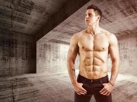 muskulös bar överkropp ung man med jeans, inomhus i tomt lager foto