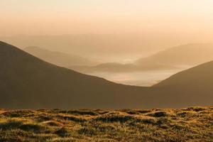 bergskedjelandskap vid soluppgång med dimma foto