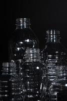 plastflaskor på svart bakgrund foto