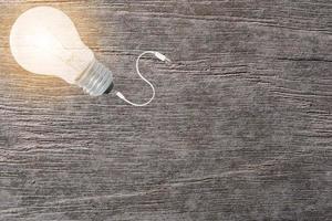 glödlampa och kabel på träbakgrund foto