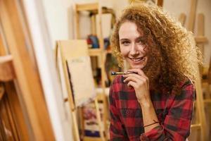 söt flicka håller en pensel nära hakan och ler