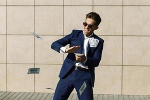 ung man i kostym med mycket pengar