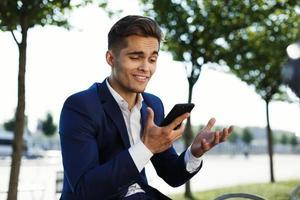 man ser förvirrad håller sin telefon