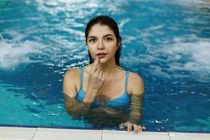 söt flicka simmar i poolen foto
