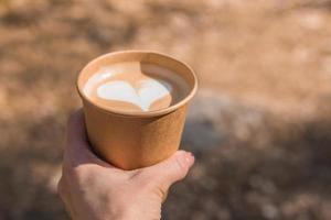 närbild av en person som håller en latte