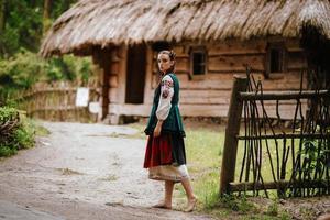 flicka i en broderad klänning som går på gården