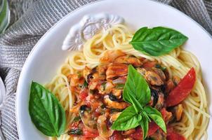pasta med musslor, pepperoni, bacon, tomat och basilika