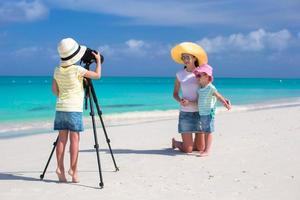 familj som tar semesterbilder på en strand