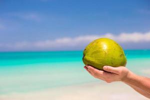 person som håller en kokosnöt på en strand