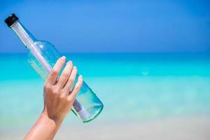 person som håller ett meddelande i en flaska foto