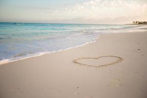 hjärta dras i sanden på en tropisk strand