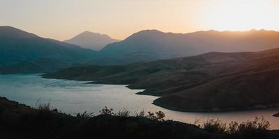 solnedgång över berg och en sjö