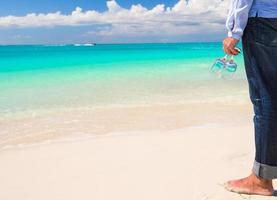 man som håller vinglas på en tropisk strand foto