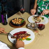 par vid middagen äter biff med vin foto