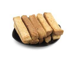staplade rostat brödpinnar på en svart platta