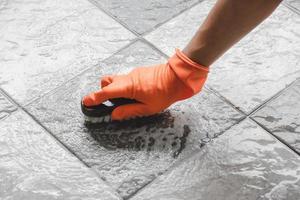 person med orange rengöringshandskar som skurar golvet