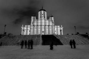 människor som står vid en kyrka på natten