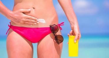 kvinna som applicerar solskyddsmedel på en strand foto