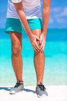 manlig idrottare som lider av knäsmärta foto