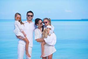 familj som bär solglasögon och vita kläder på sommarsemester