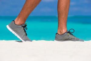 närbild av en person som bär skor på en strand
