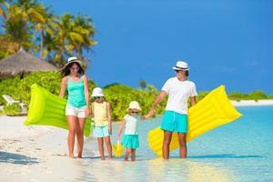 familj med floaties på stranden