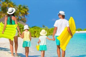 föräldrar och barn som går på en strand