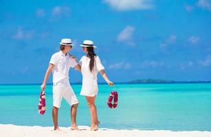 par som håller blommig leis på en strand foto