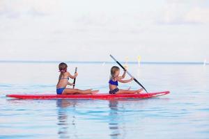 två tjejer som paddlar i havet
