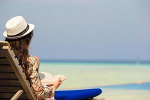 kvinna som läser en bok nära en pool foto