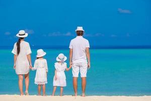 familj som står på en strand i vita kläder foto