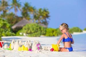 flicka som leker i vit sand på en strand foto