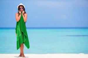 kvinna insvept i en handduk på en vit sandstrand