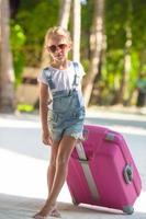 flicka med en rosa resväska